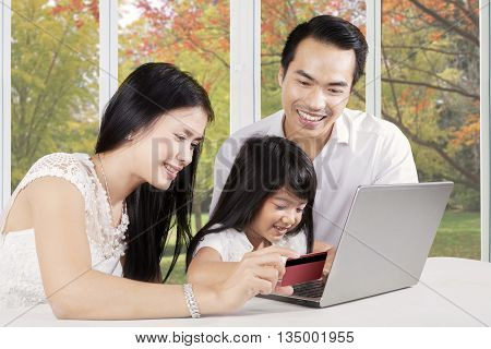 Portrait of two young parents and their daughter using credit card and laptop computer for shopping online at home