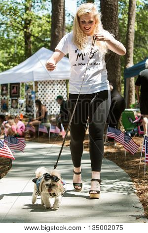SNELLVILLE, GA - MAY 14 2016:  A young woman proudly walks her dog in a dog fashion show at Pawfest a dog festival in Snellville GA on May 14 2016.