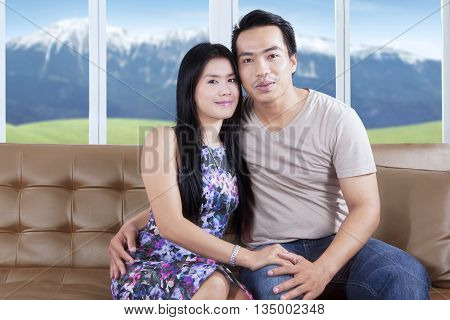 Portrait of romantic Asian couple sitting on the sofa while hugging to each other and smiling at the camera
