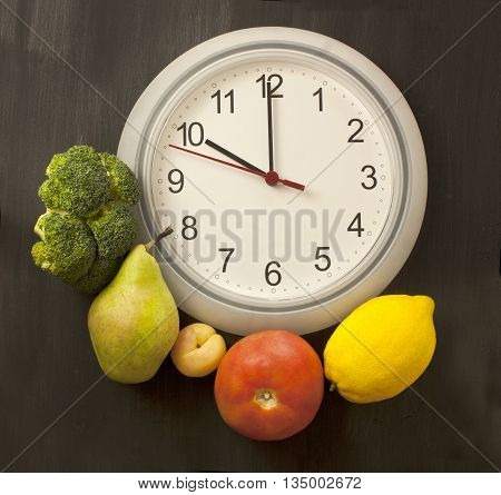 'Time to eat healthy' concept: photo of white clock shot from above on dark wooden background with fruits and vegetables around it (broccoli pear apricot tomato lemon) with copyspace around