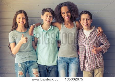 Group of teenage boys and girls is looking at camera showing Ok sign hugging and smiling while standing against gray wall
