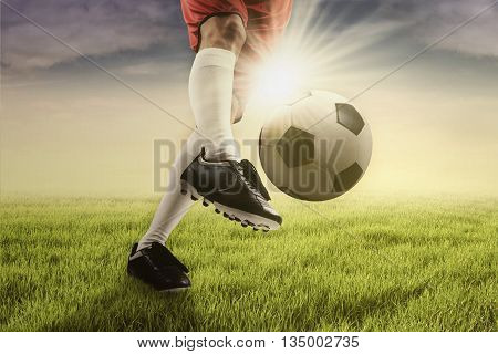 Foot of football player kicking a soccer ball on the green field shot with sunlight in the morning