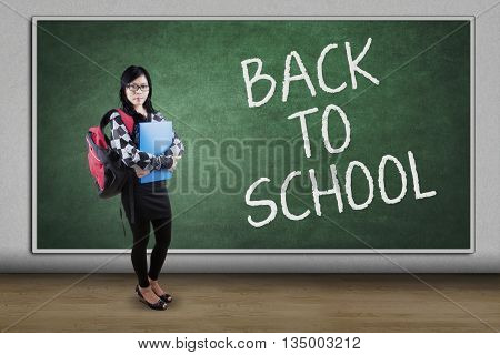 Female high school student standing in the class while carrying bag with text of Back to School on the blackboard