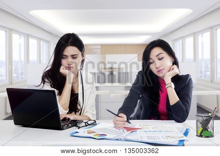 Portrait of two businesswoman tired because overworked with laptop and documents on the desk in office