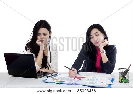 Two workers bored because overworked with laptop and documents on the desk isolated on white background