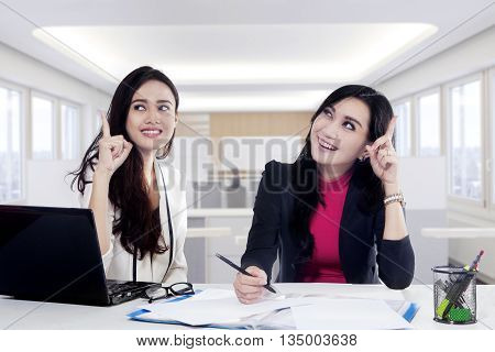 Two cheerful businesswoman get good idea while working together with laptop and documents on the desk in office
