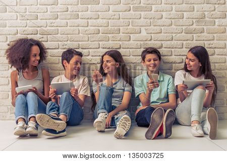 Group of teenage boys and girls is using gadgets talking and smiling sitting against white brick wall