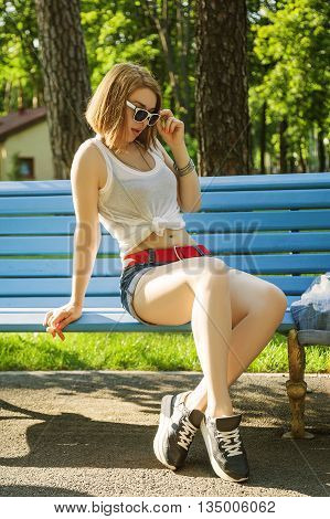 sexy girl in shirt tiedand shorts with red belt and bare bellysitting relaxed on a bench in the park and looks down lowered her sunglasses and holding a candy on a stick