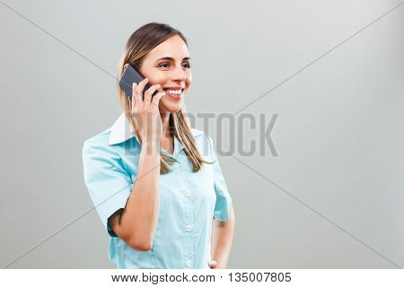 Beautiful nurse talking on mobile phone with someone.