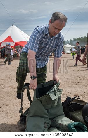 Tyumen Russia - June 11 2016: Race of Heroes project on the ground of the highest military and engineering school. Exhibition of weapon. Man - visitor of show tries on the sapper suit