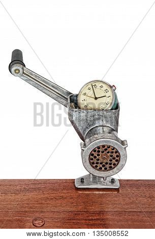 Alarm clock in meat grinder on white background.Toned image.