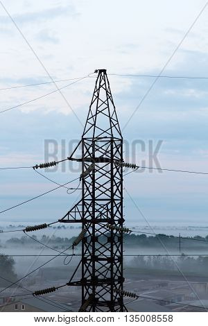 Electricity pylon against of cloudy sky taken closeup.