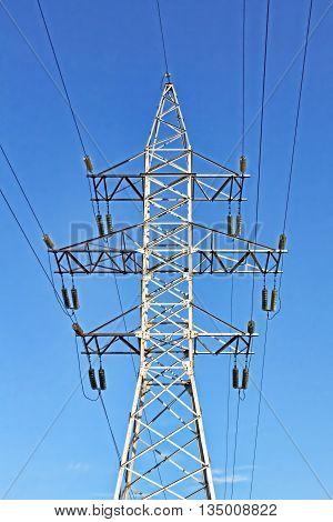 Electricity pylon taken closeup against of blue sky.