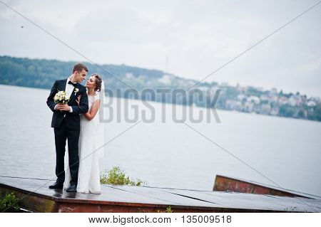 Young wedding couple at the pier at wedding