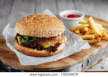 Hamburger With Tomato And Cheese, French Fries And Ketchup On A Wooden Board