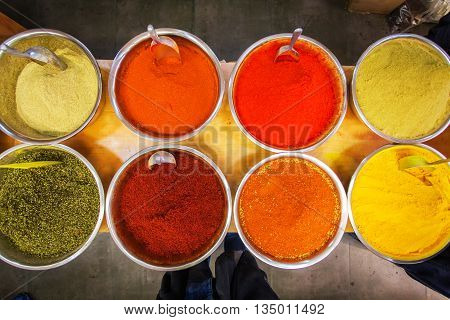 Close-up of different spices in bowls to prepare delicious food. The counter on the Mahane Yehuda Market in Jerusalem, Israel. Top view.