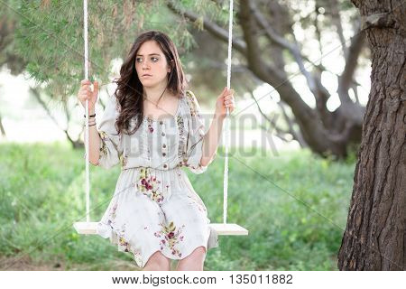 Serious Woman Sitting on a Swing in a Park