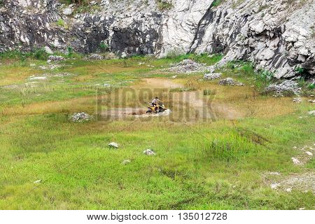 Man In Off Road Quad Bike Through A Mud Lake