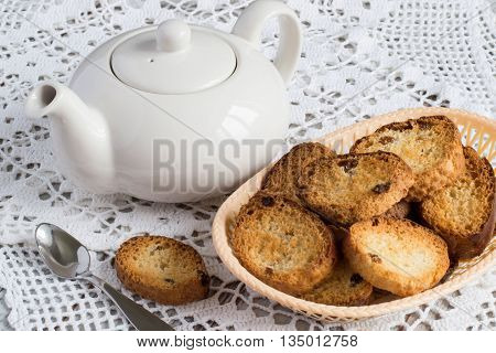 Homemade rusks in a basket and a teapot on a white openwork tablecloth.