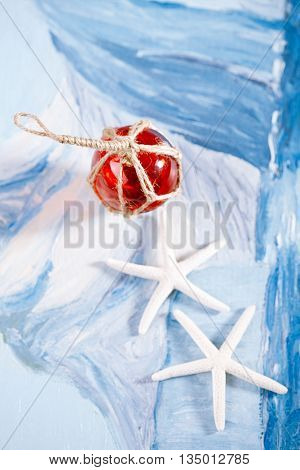 white starfish with red Glass float on blue painted background