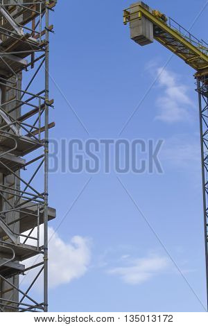 Construction scaffolding and crane element. Blue sky background. Construction or reconstruction concept