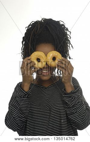 Teenage girl playing with donuts on white background