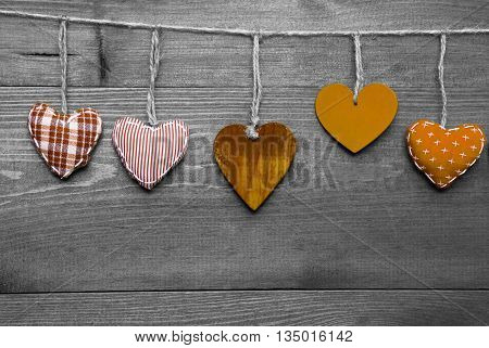 Wooden Background With Orange Hearts Hanging In A Row. Black And White Style With Colored Hot Spots. Copy Space For Advertisement Or Free Text. Greeting Card For Valentines Or Mothers Day