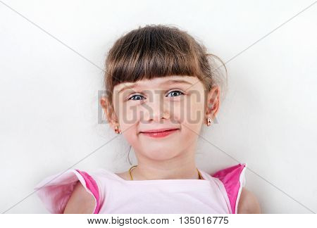 Cheerful Little Girl Portrait on the White Wall Background