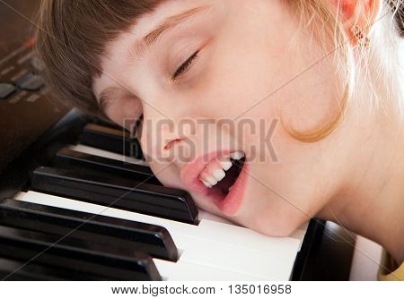Tired Small Girl sleep on the Piano Keyboard