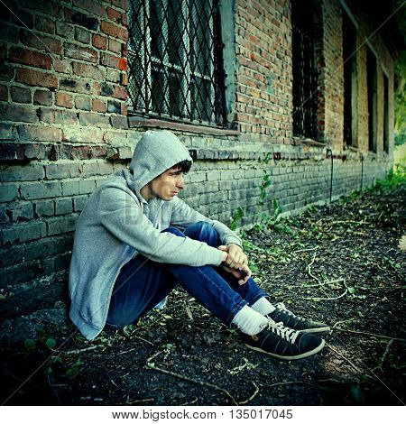 Toned Photo of Sad Teenager sit near the Brick Wall of the Old House