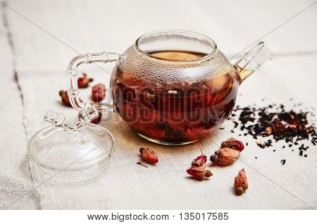 The Dry Red Small Roses in the Glass Teapot,Tea Drinking,Table Rough Linen Tableclose;Wooden Plate