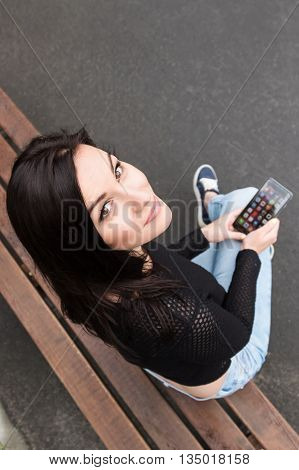 Young brunette woman sitting on a bench with a smartphone in hand and looking up at the camera
