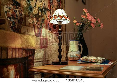 Table lamp a vase of carnations and a statue of a black cat on the table at the tapestry