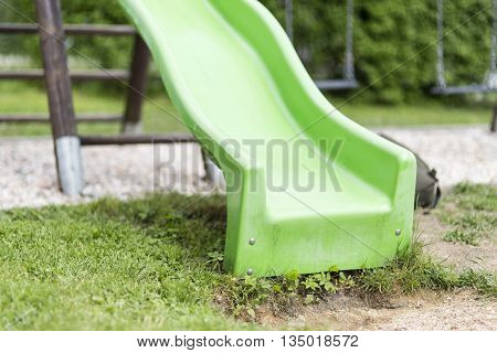 Green child slide on playground entertaiment tool