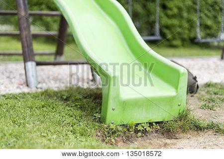 Green child slide on playground entertaiment tool