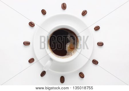 Cup of strong coffee with foam on saucer and coffee beans against white background forming clock dial viewed from above