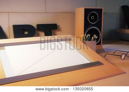 Closeup of blank table easel on designer's desktop with stationery items glasses and loudspeakers. Mock up 3D Rendering