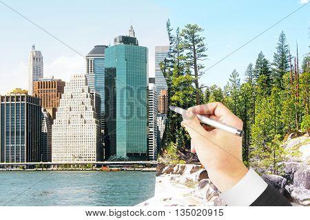 Man's hand drawing modern city on landscape. Concept of urbanization