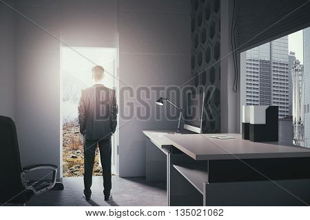 Businessman standing in modern office interior with open door looking at landscape. Concept of choice between career development and traveling. 3D Rendering