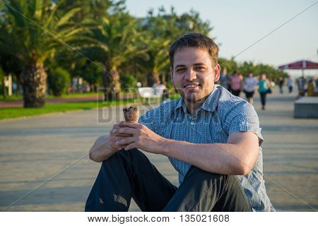 Happy handsome young man eating ice- cream outdoors.