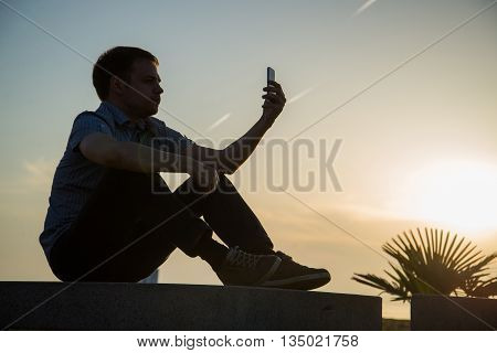 Young guy is watching photos on mobile phone what he took now during rest near sea with copy space background for your advertising text message or content.