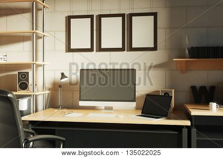 Creative designer desktop with blank computer monitor laptop loudspeaker coffee cup and other items on brick wall background with three picture frames. Mock up 3D Rendering