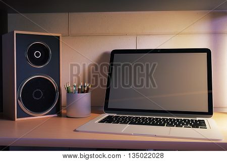Closeup of blank laptop on creative desktop with loudspeaker and pencils at night. Mock up 3D Rendering