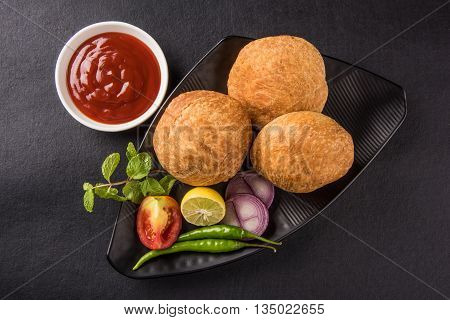 Kachori or Kachauri or Kachodi or Katchuri is a spicy snack popular in india, asian snacks, pakistani snacks with tea and green salad and tomato ketchup, over black background
