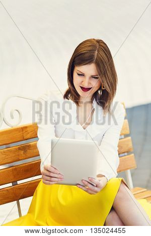 Student girl or young woman in white blouse uses tablet pc. Woman with tablet sitting on the bench in the park. Young woman student surf internet outdoors, web communication.