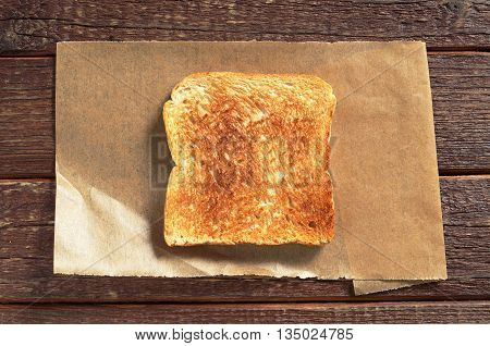 Slice of toasted bread on wooden table top view