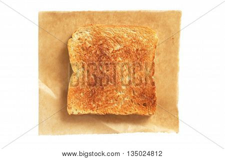 Slice of toasted bread on paper isolated on white background top view