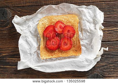 Slice of toasted bread with strawberries on crumpled paper on table top view