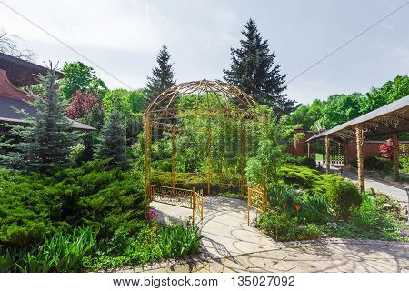 Beautiful landscape design, garden path to metal gazebo and evergreen trees in sunlight.