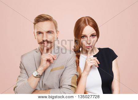 Woman and man keep secret. Couple shows hush sign, adultery, relationship issue, Young beautiful couple isolated at pink